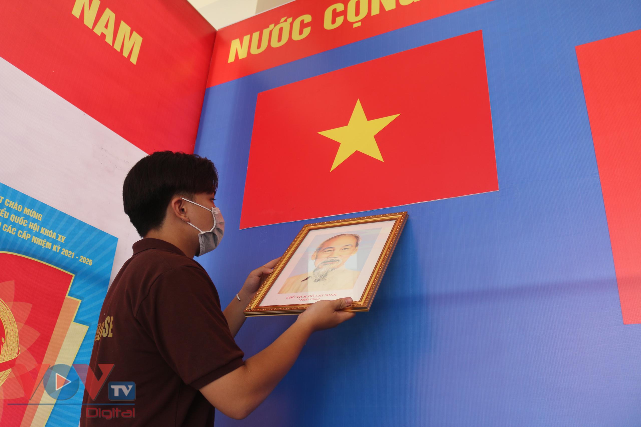 Nhiều điểm bầu cử đang hoàn tất các công đoạn chuẩn bị. Trong ảnh, một bạn trẻ đang treo ảnh Bác Hồ, trang trí phông khu vực bỏ phiếu